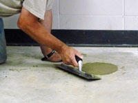 Repairing the cored holes in the concrete slab floor with fresh concrete and cleaning up the Iron River home.