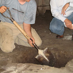 Digging a hole for the engineered fill used in a crawl space support system installation in Eagle River