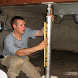 A contractor in Minocqua installing a crawl space jack post.