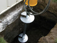 Installing a helical pier system in the earth around a foundation in Escanaba
