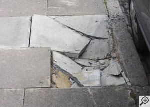 photo of a sinking concrete sidewalk with cracks in Lac Du Flambeau