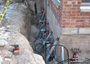 Foundation push piers installed around a house with a foundation settlement issues in Butternut