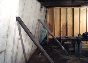 A severely tilting foundation wall propped up by steel beams in Calumet.