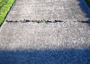 A sinking concrete sidewalk in need of mudjacking services in Ashland.