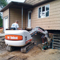 Excavating to expose the foundation walls and footings for a replacement job in Minocqua