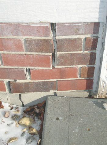 Severe street creep damage to a garage wall outside a Mercer home
