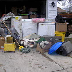 Soaked, wet personal items sitting in a driveway, including a washer and dryer in Eagle River.