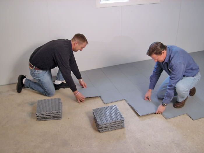... Top · Contractors Installing Basement Subfloor Tiles And Matting On A  Concrete Basement Floor In Ironwood, Michigan